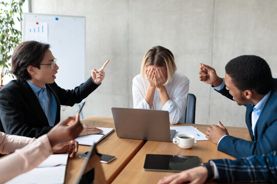 Colleagues Shouting At Unhappy Victimized Businesswoman Sitting In Modern Office