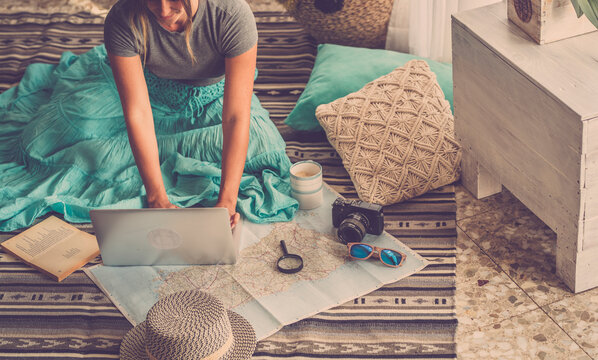 Caucasian woman planning vacation travel with laptop and map guide at home, female people plan next holidays vacation while relaxing on the floor - pretty girl wanderlust concept