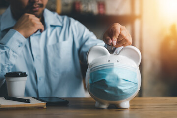 Obraz businessman putting coin on piggy bank wearing surgical face mask. Global economy during coronavirus pandemic. Financial crisis, Financial Despair, banking concept. saving and investment. - fototapety do salonu