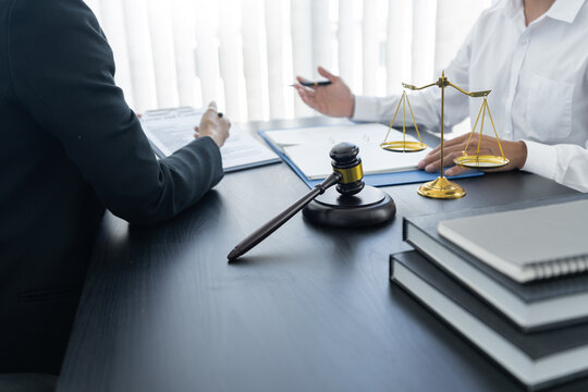 law,libra scale and hammer on the table, 2 lawyers are discussing about contract paper, law matters determination, open hands.