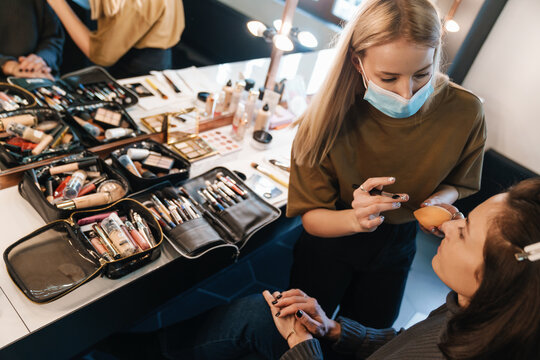 Blonde woman in face mask doing makeup for her client in beauty salon