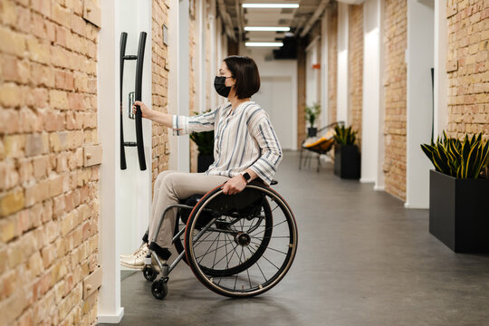 White young woman wearing face mask in wheelchair opening door