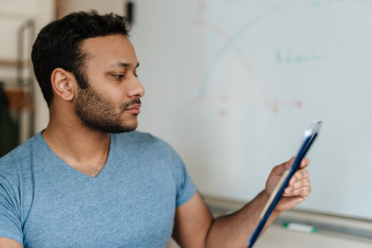Middle eastern man working with tablet computer while sitting at desk