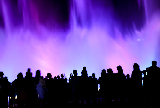 Silhouettes of people at a colored fountain at night.
