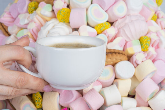 Woman's hand with a cup of coffee on the background of marshmallows, close-up.Holiday concept, congratulations.