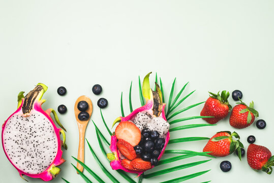 Background with Exotic Fruit Salad Served in Half a Dragon Fruit and Raw Strawberry and Blueberry on Light Green Background Top View Horizontal Copy Space Healthy Diet Dessert