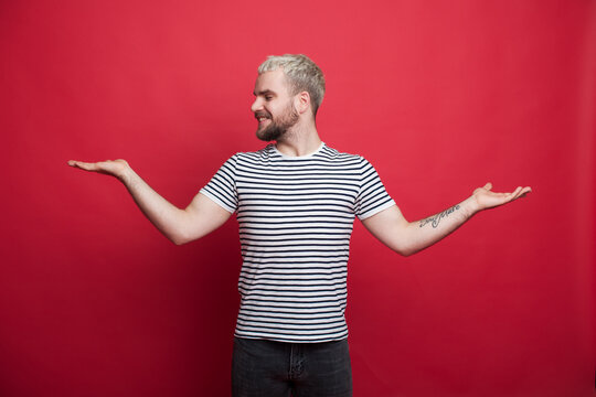 Caucasian bearded man is smiling while holding something and comparing in palms posing on a dark red studio wall