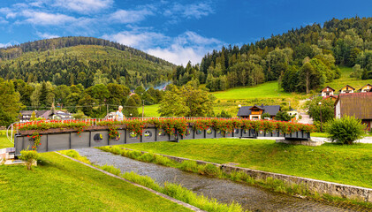 Panoramic view of Beskidy Mountains surrounding Szczyrk mountain resort with bridge over Zylica creek in Beskidy Mountains in Silesia region of Poland