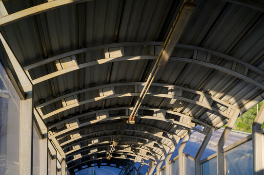 metal outdoor canopy for protection from the sun and bad weather with lamps on the ceiling, industrial roof for pedestrian safety