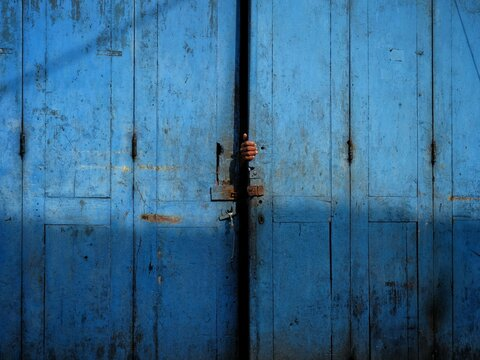 Cropped Hand Of Person Behind Door