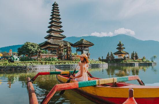 Woman In Outrigger At Pura Ulu Danau Temple Against Sky