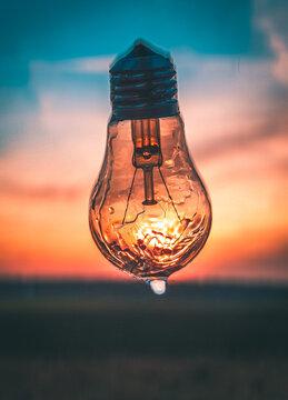 Close-up Of Illuminated Light Bulb On Field