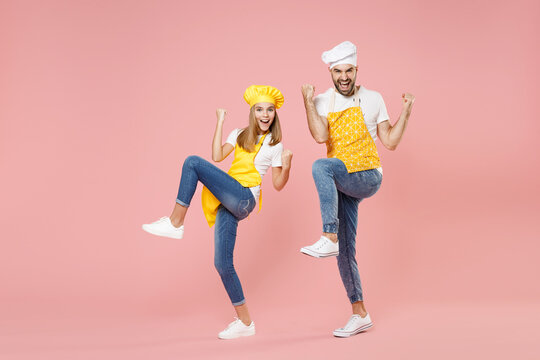 Full length teen fun girl dad man father's helper chef cook confectioner baker in yellow apron cap do winner gesture celebrate clench fist with raised legs isolated on pink background studio portrait.