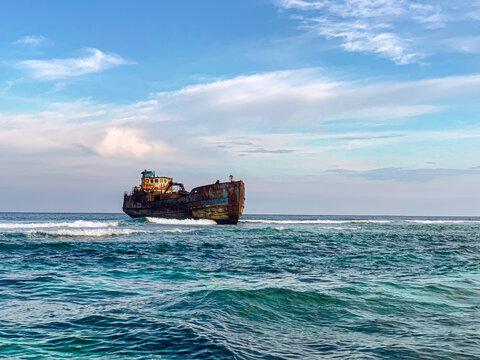 Ship sailing on blue ocean waves under a cloudy sky