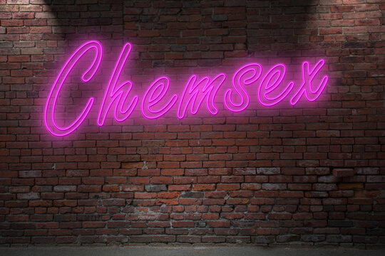 Neon BDSM Chemsex lettering on Brick Wall at night