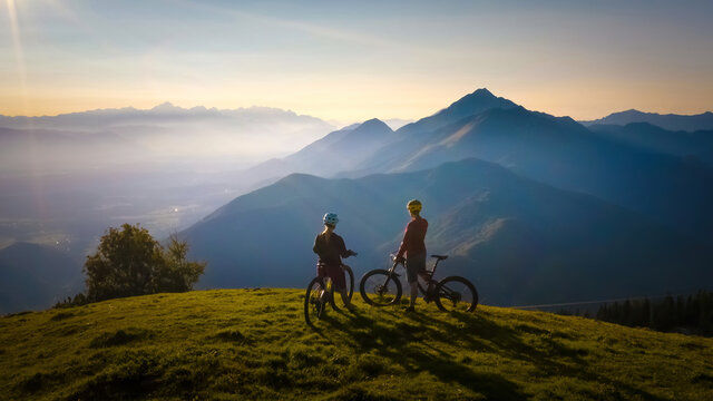 Two females on mountain bikes talking and looking at beautiful sunset