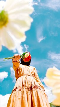Low Angle View Of Woman Holding Flower Against Sky
