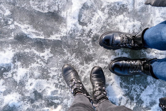 Two Girls Looking Down At Feet. Frozen Lake Or River. Feet On Ice. Wearing Snow Shoes And Standing