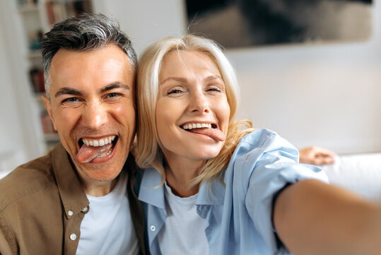 Funny married mature couple, middle aged caucasian husband and wife fooling around, taking a selfie on smartphones, showing their tongues, making faces, having fun together