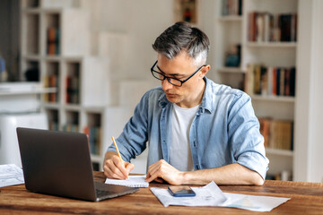 Fototapeta Focused mature gray haired intelligent caucasian businessman or freelancer with glasses, sitting at workplace, taking notes in notebook, studying or working online, using laptop