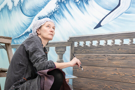 Mature Woman Artist Draws Thoughtful Looking At Her Work - A Mural On The Marine Theme