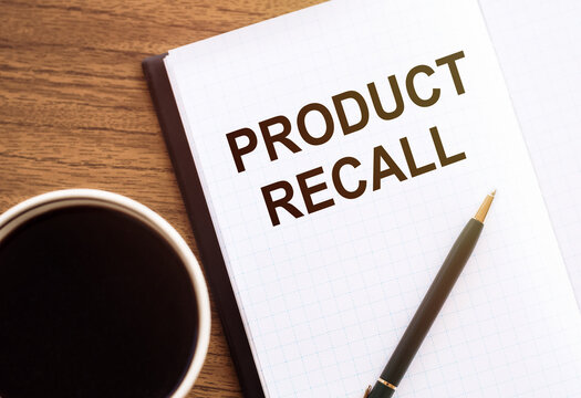 PRODUCT RECALL - text on notepad on wooden desk.