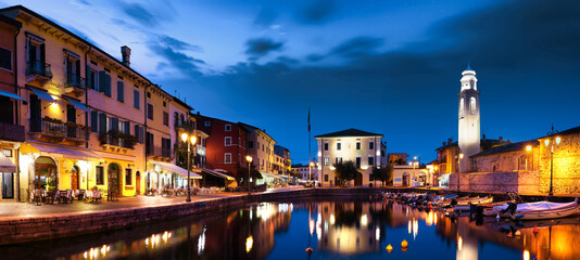 Fototapeta Boats in old town port of Lazise at twilight. The town is a popular holiday destination in Garda Lake district.