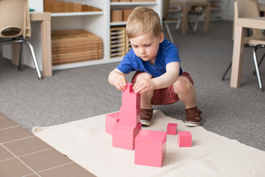 Little boy building iconic Montessori pink tower