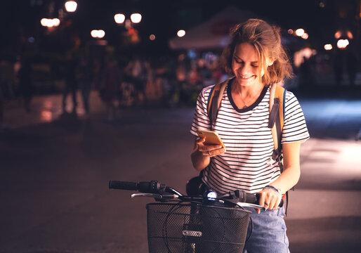 Beautiful happy smiling young woman using bike rental app in night european city