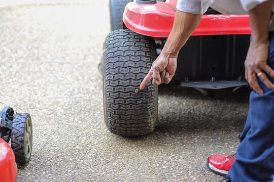 Man Pointing His Finger At A Punctured Tire With A Nail Stuck In A Wheel On Lawnmower Tire