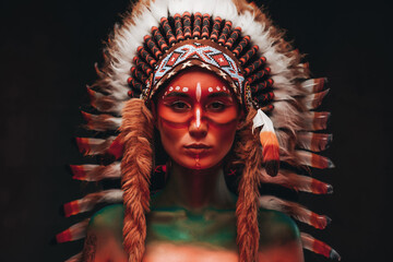 Fototapeta Tribal woman warrior with headwear from feathers in dark background obraz