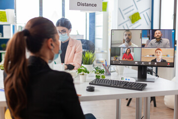 Fototapeta Back view of woman talking with team during remote video conference in new normal office in timp of global pandemic with coronavirus, keeping social distancing wearing face mask. obraz