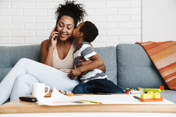 Fototapeta Black smiling woman talking on cellphone while hugging her son at home