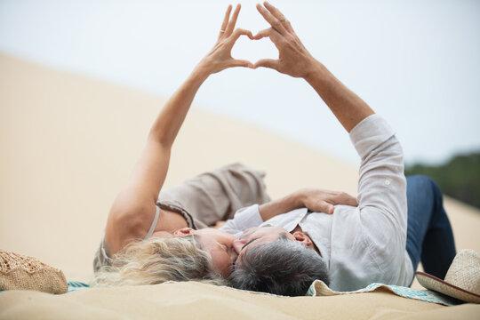 senior couple enjoying beach holiday laying on dune