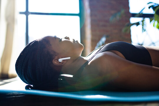 african american woman in black sporty bra is lying down on yoga mat floor closed eyes and listening an audio meditate mantra
