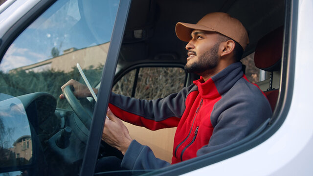 Happy indian courier using tablet in the van . High quality photo