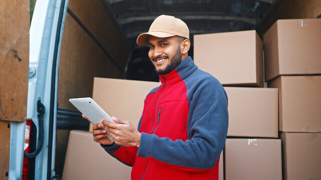 Delivery man using tablet to preview orders. Standing in front of the van with parcels. High quality photo
