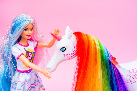 Nice, FRANCE - 12.04.2021: Portrait of blond rainbow Barbie doll with Unicorn against pink background.