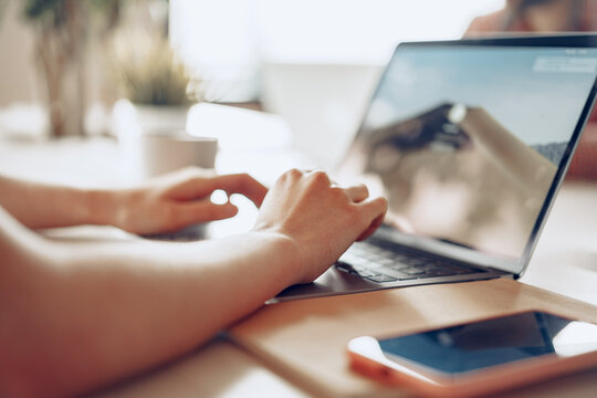 Close up of a woman typing on laptop while sitting at the table in office