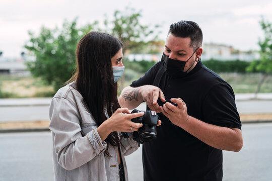 Chico con mascarilla por covid 19 dando indicaciones a una chica con mascarilla con una cámara de fotos