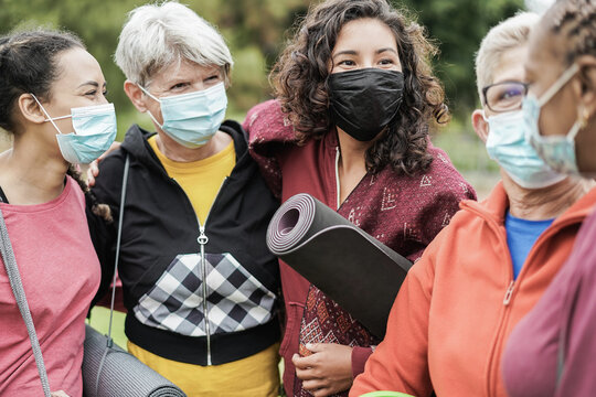 Multi generational women having fun before yoga class wearing safety masks during coronavirus outbreak at park outdoor - Main focus on center girl face