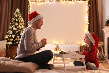 Fototapeta Father and daughter near video projector screen at home. Cozy Christmas atmosphere