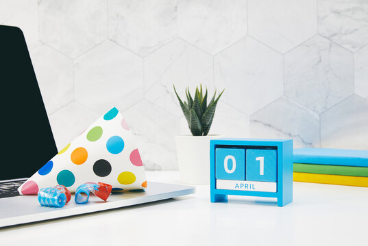 April fool's day with a blue cube calendar, colorful festive hat and other objects on a working desk