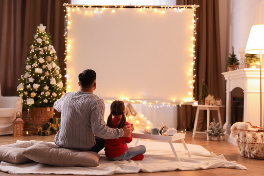 Father and daughter watching movie using video projector at home. Cozy Christmas atmosphere