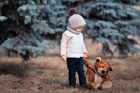 Baby and his friend bear in the park. Winnie the Pooh. Spring walk of a child with a toy. Based on a fairy tale. Brown teddy bear and a boy in a knitted hat and jacket