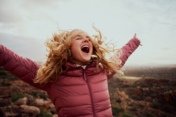 Close-up of a beautiful woman on mountain trail with her hair flying and hands outstretched with mouth open