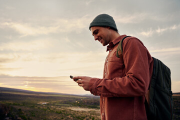 Fototapeta Happy male hiker using smartphone on mountain top