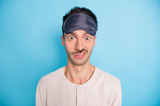 Portrait of nice puzzled brunet guy wearing sleep mask cant asleep dislike isolated over bright blue color background