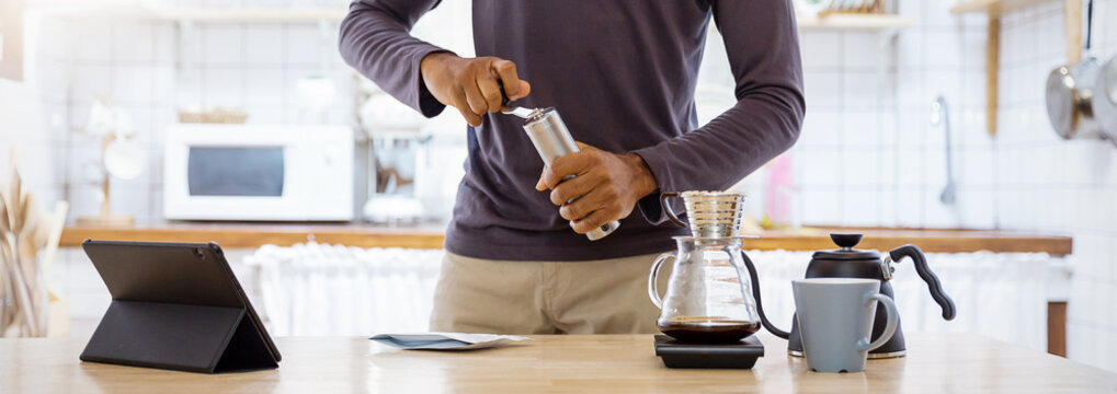 Startup small business owner african black man hand hold grinding coffee beans manual stainless steel in coffee shop.  Man barista cafe owner banner concept