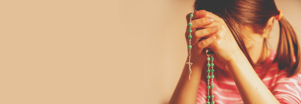 Young girl holding rosary and praying to God.